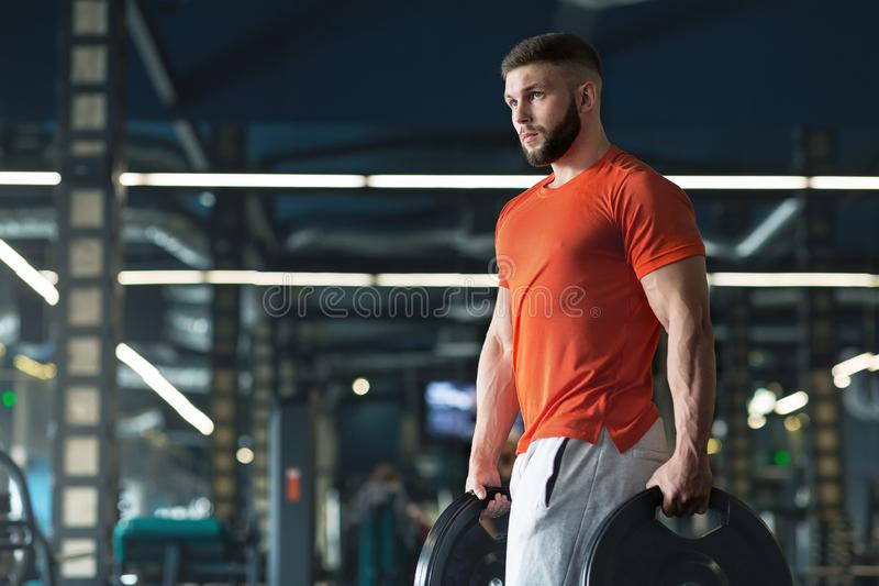 Attractive muscular bodybuilder doing heavy deadlifts in modern fitness center stock photos