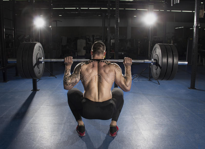 Attractive muscular bodybuilder doing heavy squat exercise in mo stock images