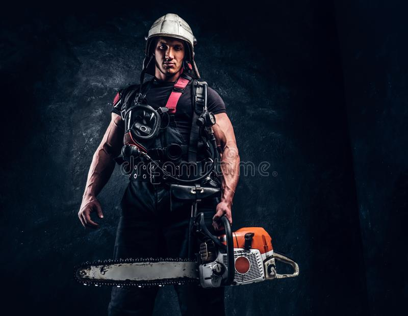 Portrait of muscular man with chainsaw and respirator stock photos