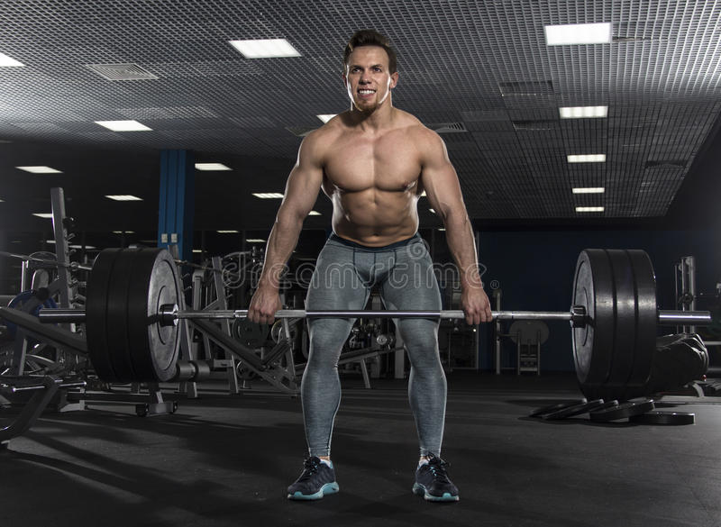 Attractive muscular shirtless athlete doing heavy deadlift exer royalty free stock images