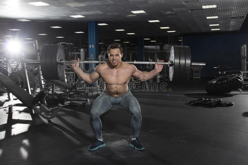 Attractive muscular shirtless athlete doing heavy squat exercis royalty free stock photos