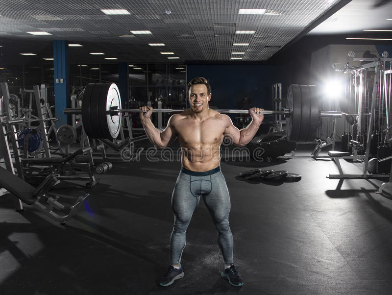 Attractive muscular shirtless athlete doing heavy squat exercis stock photography