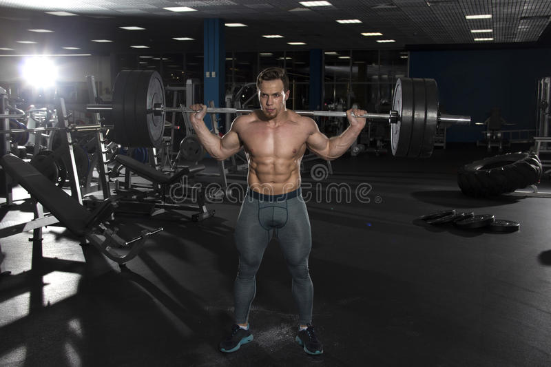 Attractive muscular shirtless athlete doing heavy squat exercis royalty free stock photo