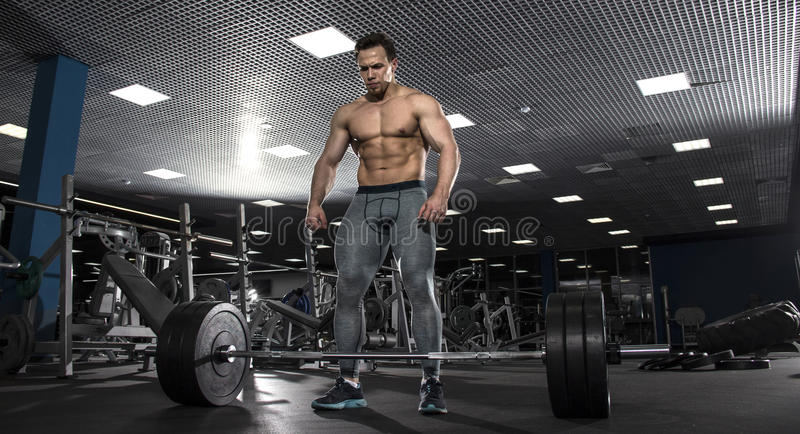 Attractive muscular shirtless athlete preparing to do deadlift i stock photo