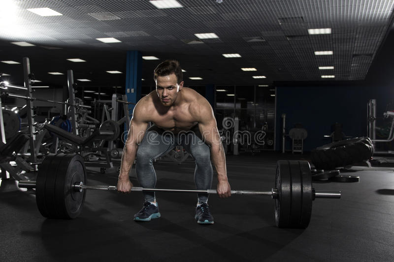 Attractive muscular shirtless athlete preparing to do heavy dea royalty free stock photography