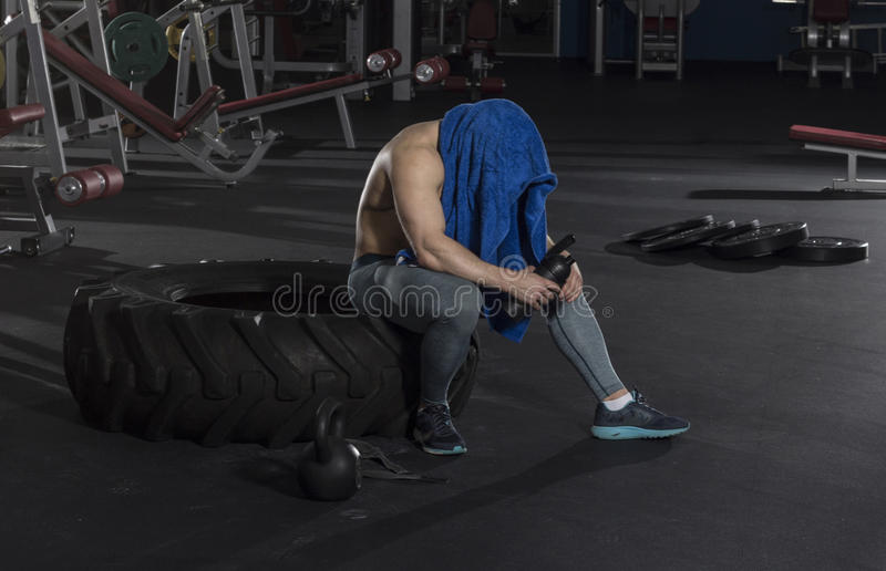 Attractive muscular shirtless athlete taking the break from heav stock photo