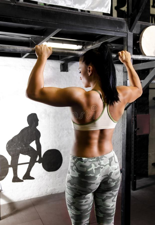 Attractive muscular woman, holding on pull ups bar stock image