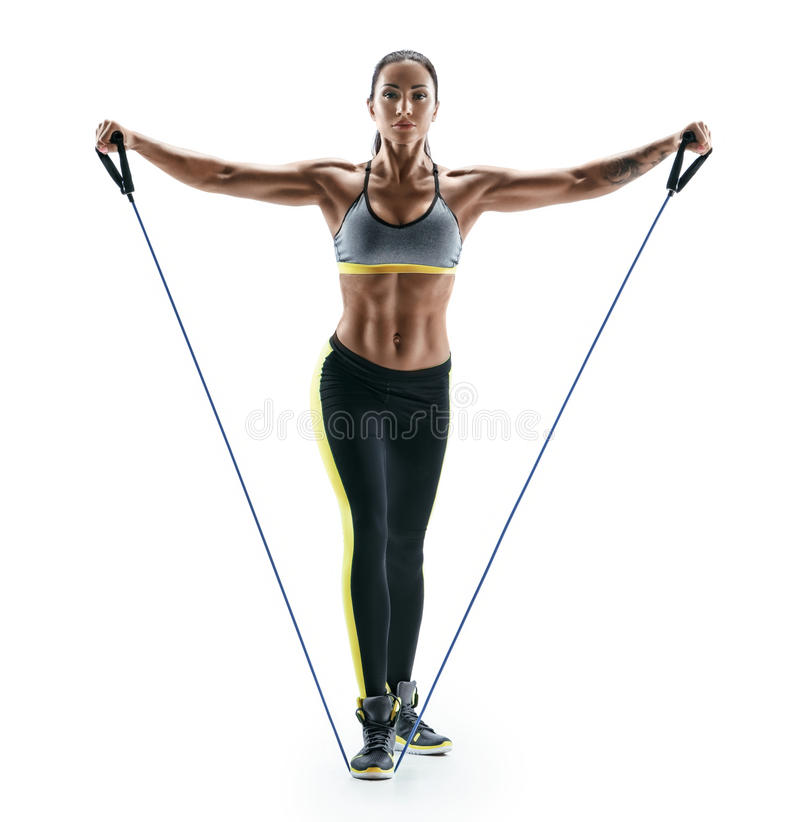Attractive muscular woman performs exercises for deltoid muscles using an resistance bands. Photo of young brunette isolated on white background. Strength and stock photo