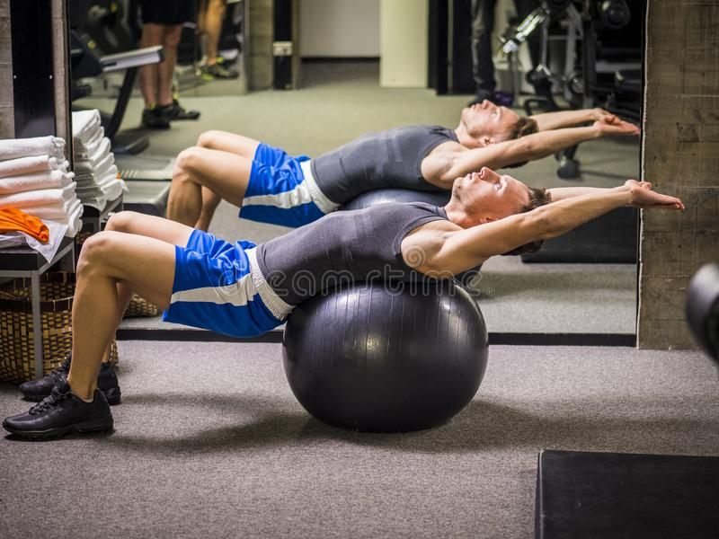 Handsome young man doing abs exercises on ball. Attractive muscular young man in gym working out, doing exercises for abs on inflatable ball stock image