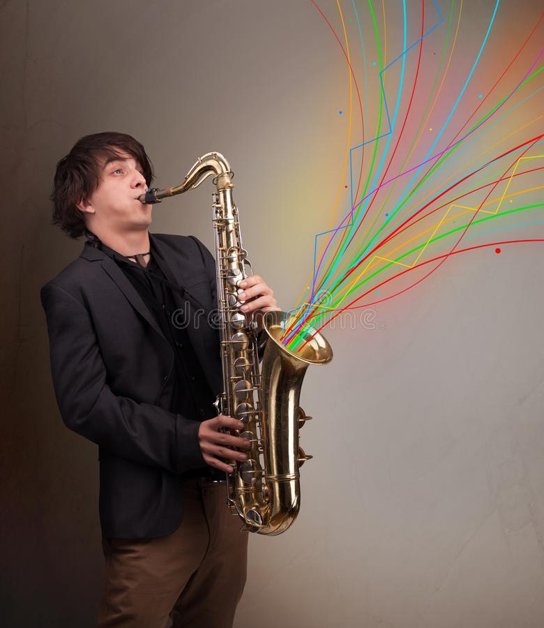 Attractive musician playing on saxophone while colorful abstract. Attractive young musician playing on saxophone while colorful abstract lines exploding stock image