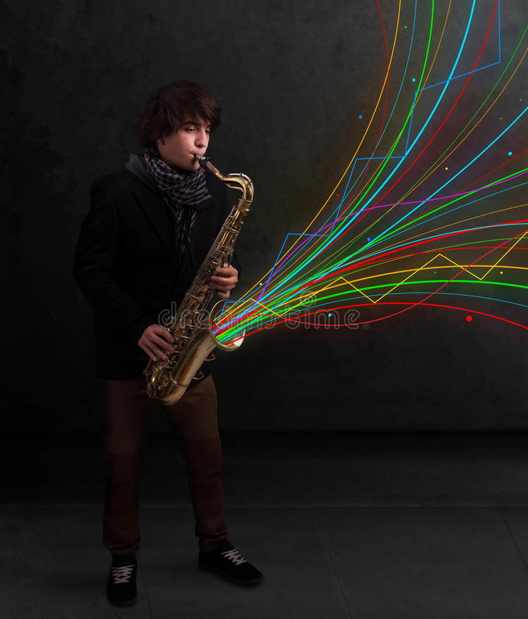 Attractive musician playing on saxophone while colorful abstract. Attractive young musician playing on saxophone while colorful abstract lines exploding royalty free stock photography