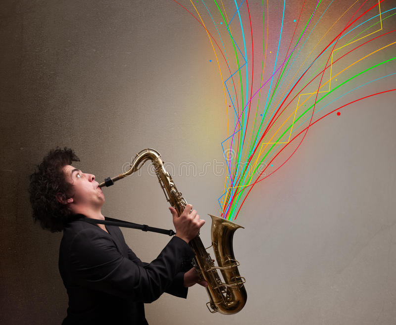 Attractive musician playing on saxophone while colorful abstract stock photography