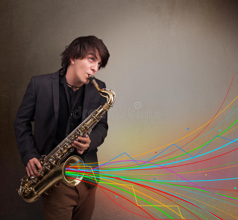 Attractive musician playing on saxophone while colorful abstract. Attractive young musician playing on saxophone while colorful abstract lines exploding royalty free stock image