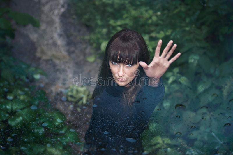 Attractive mysterious young woman with raised left hand in a beautiful rainy park stock images