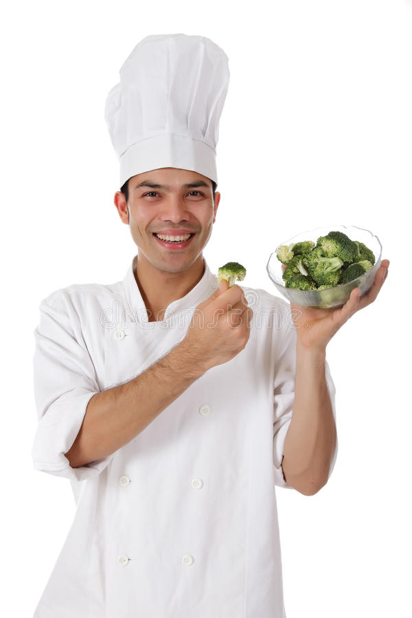 Attractive nepalese chef male, broccoli. Attractive young nepalese chef male with uniform and hat presenting fresh broccoli in a bowl. Studio shot. White stock images