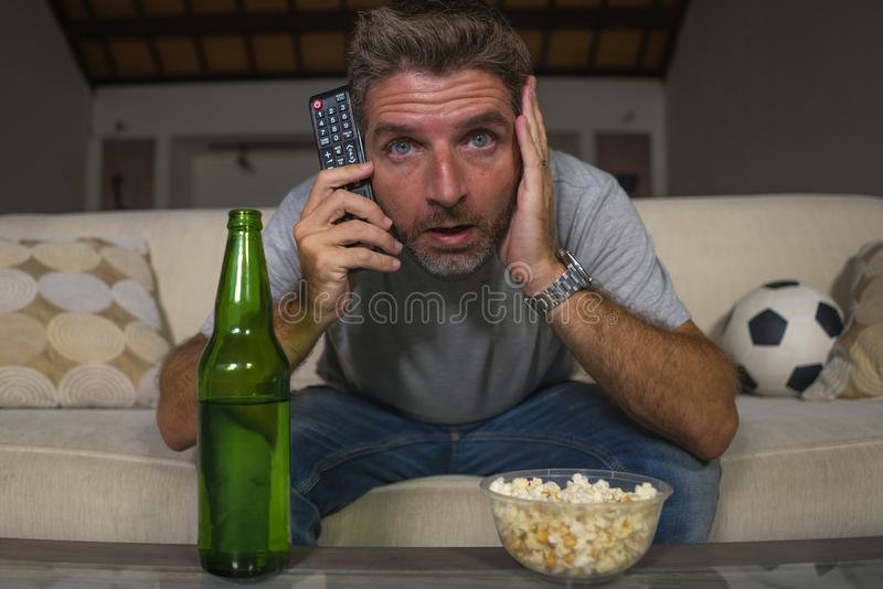 Attractive nervous and excited football supporter man watching soccer game on television at home sofa couch in stress and emotion. Lifestyle portrait of young royalty free stock photography