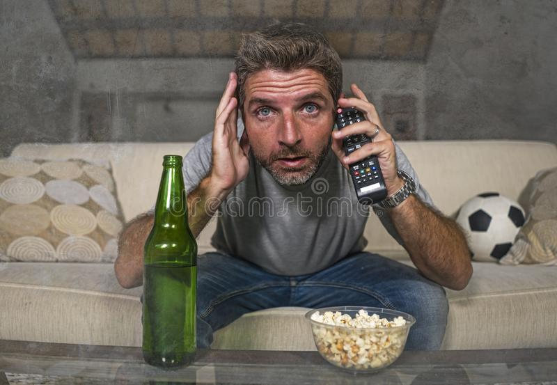 Attractive nervous and excited football supporter man watching soccer game on television at home sofa couch in stress and emotion. Lifestyle portrait of young stock image