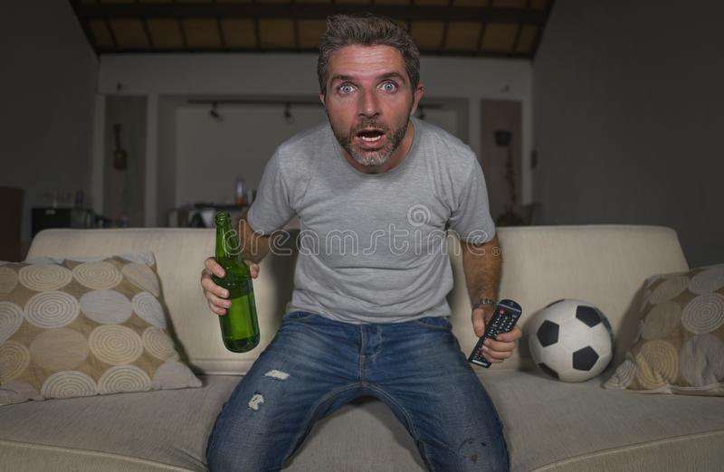 Attractive nervous and excited football supporter man watching soccer game on television at home sofa couch in stress and emotion. Lifestyle portrait of young royalty free stock images