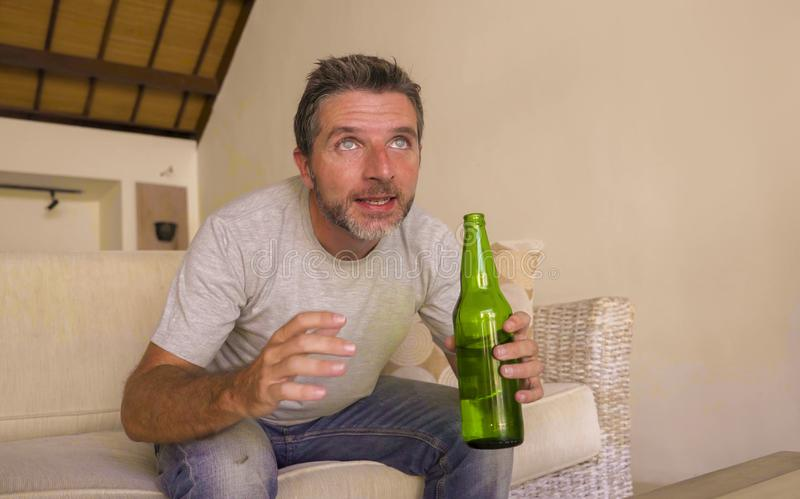 Attractive nervous and excited football supporter man watching soccer game on television at home sofa couch in stress and emotion. Lifestyle portrait of young stock photos