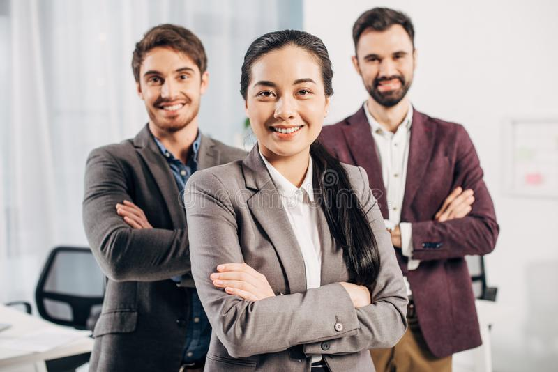 Attractive office manager with arms crossed looking at camera with smiling coworkers royalty free stock image