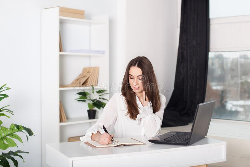 Attractive office worker standing. The girl writes in a notebook. Close-up portrait of an office worker. Positive young manager wo. Rking on business project in stock photos