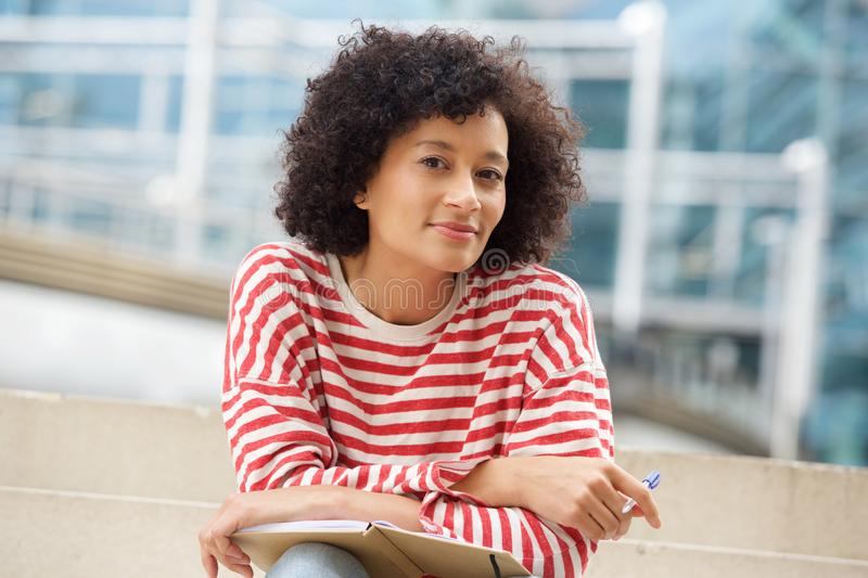 Attractive older african american woman sitting outdoors with book and pen stock images