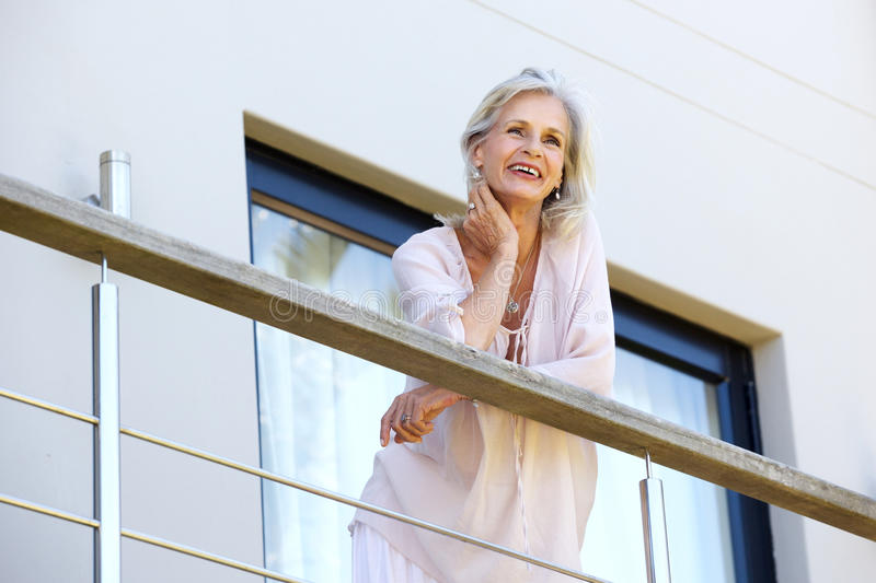 Attractive older woman resting head on hand standing on terrace. Portrait of attractive older woman resting head on hand standing on terrace royalty free stock photo