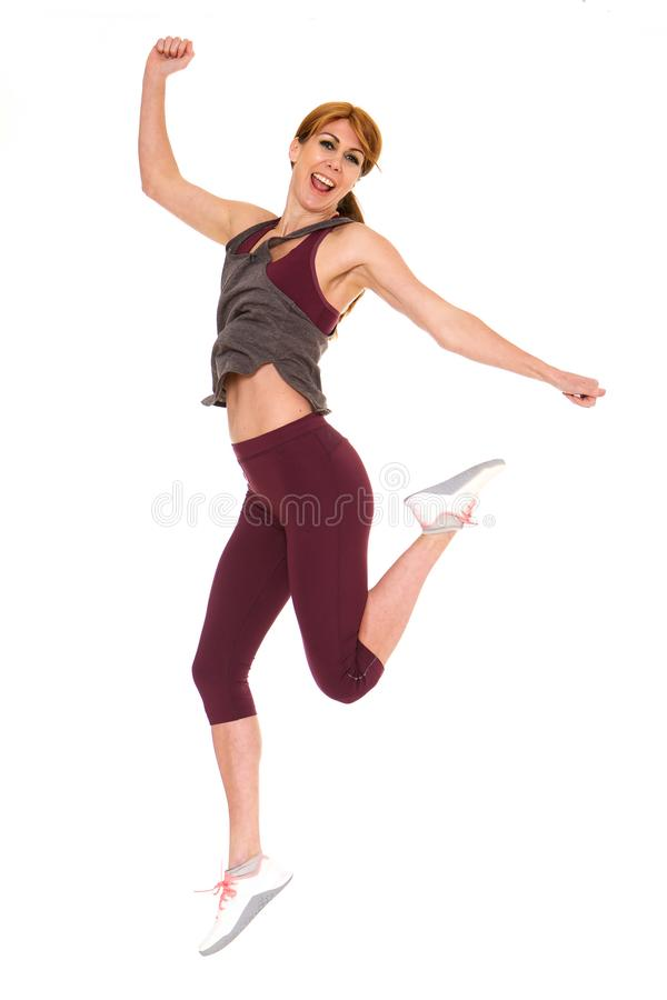 Attractive older woman in sportswear jumping stock photos