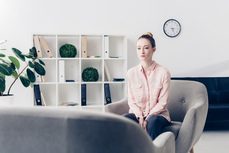 Attractive pensive businesswoman sitting in armchair in office and. Looking away stock image