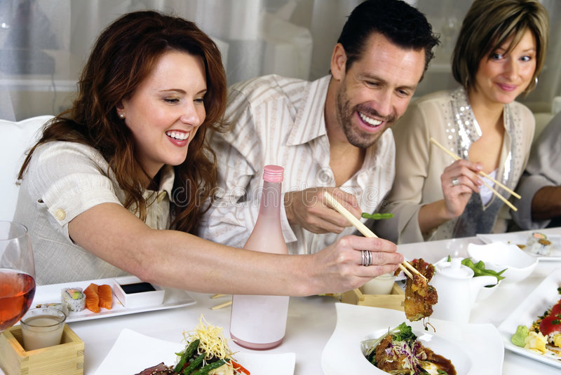 Attractive people eating and socializing. Group of attractive people eating and socializing at a restaurant royalty free stock photography