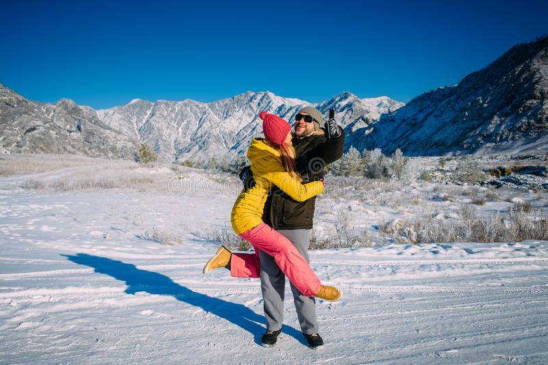 Attractive people having fun on the background of snow-capped peaks. Couple in love dressed in bright clothing hugs against snow royalty free stock photography