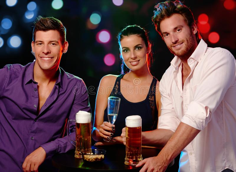 Attractive people in nightclub. Attractive young people smiling, drinking in nightclub royalty free stock image