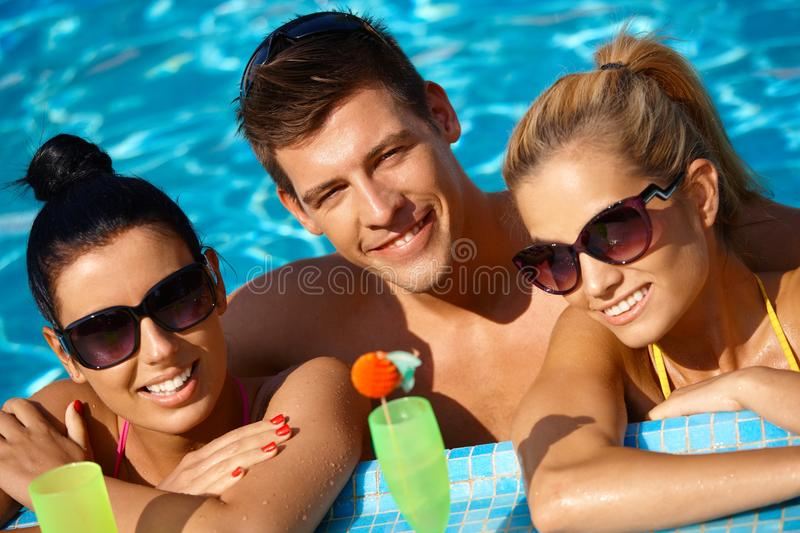 Attractive people in pool smiling. Attractive young people smiling in swimming pool, drinking cocktail stock photography