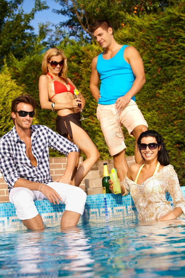 Attractive people at summertime. Attractive young people enjoying summer holiday by outdoor swimming pool, smiling royalty free stock image