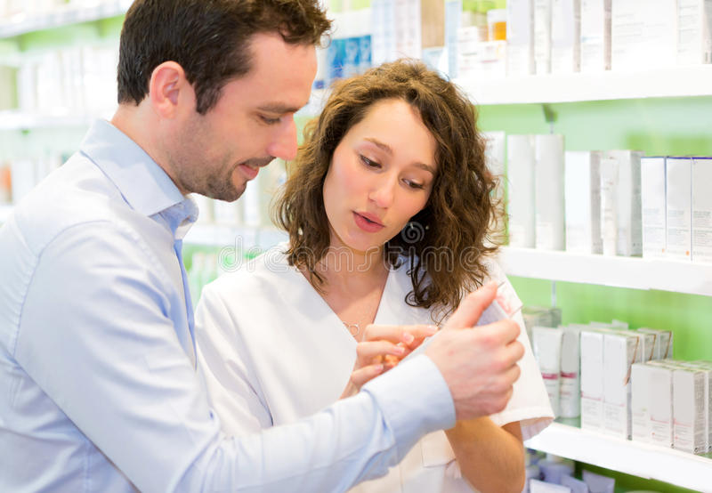 Attractive pharmacist advising a customer stock photography