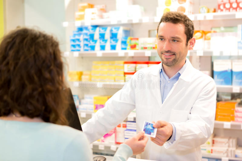 Attractive pharmacist taking healt credit card stock images