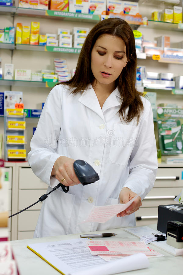 Attractive pharmacist working with prescription stock photo