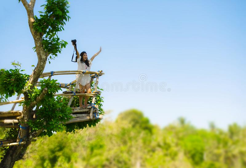 Attractive photographer woman holding with reflex camera spreding arms free at high viewpoint with beautiful landscape of trees i royalty free stock photography