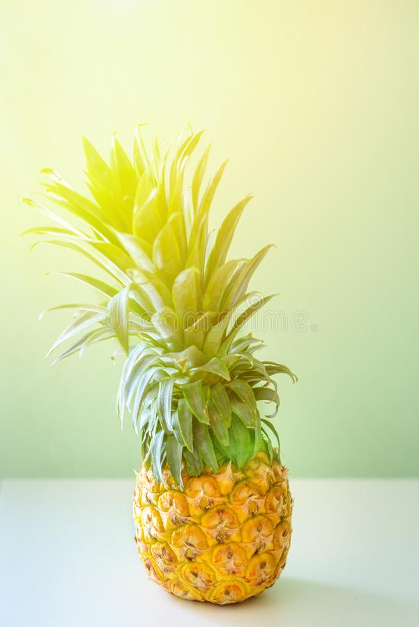 Attractive pineapple on the table against mint background.Tropical summer vacation concept, healthy food, wellbeing. royalty free stock photography