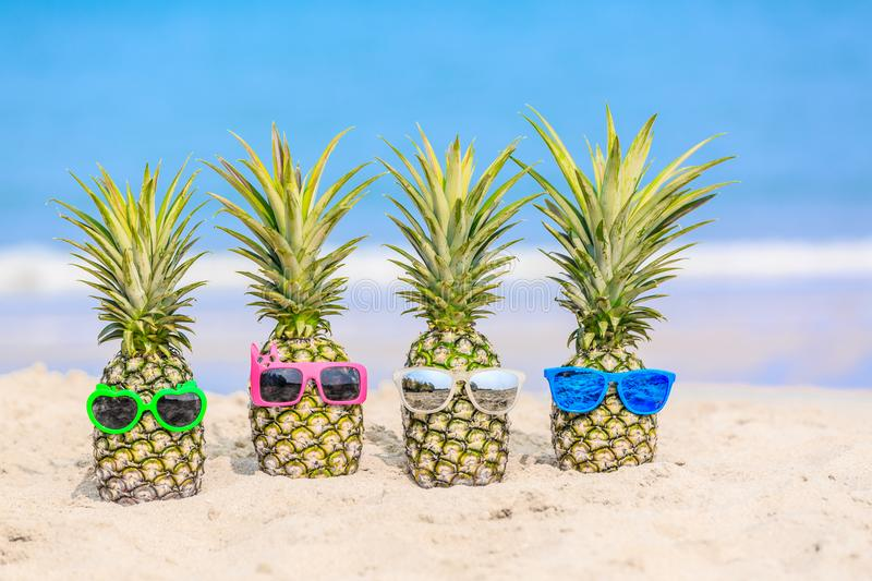Attractive pineapples on the beach against turquoise sea. Wearing stylish mirrored sunglasses. Tropical summer vacation concept. Sunny day on the beach of stock photography