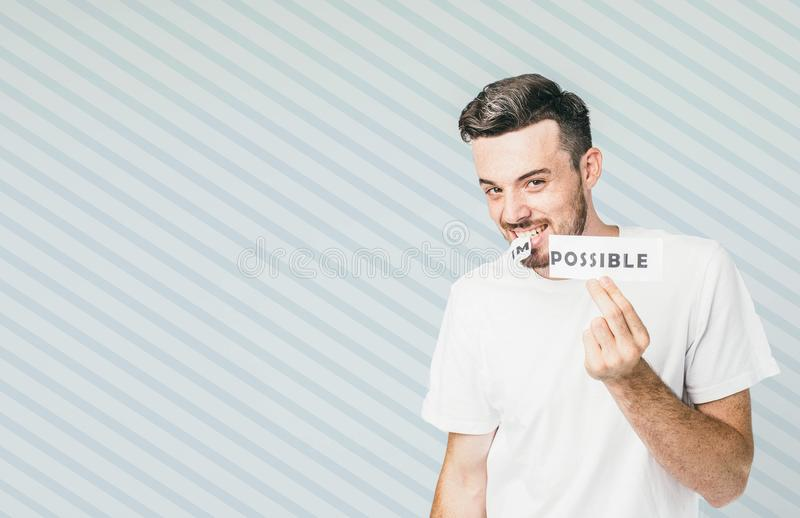 Attractive and posistive guy is standing at the white wall and holding a piece of paper in his hand and rest of it with. His teeth. It was said Impossible but royalty free stock photos