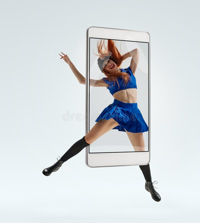 Female dancer jumping. Attractive positive woman in police uniform jumping while dancing, concept virtual reality of the smartphone. going out of the device stock image
