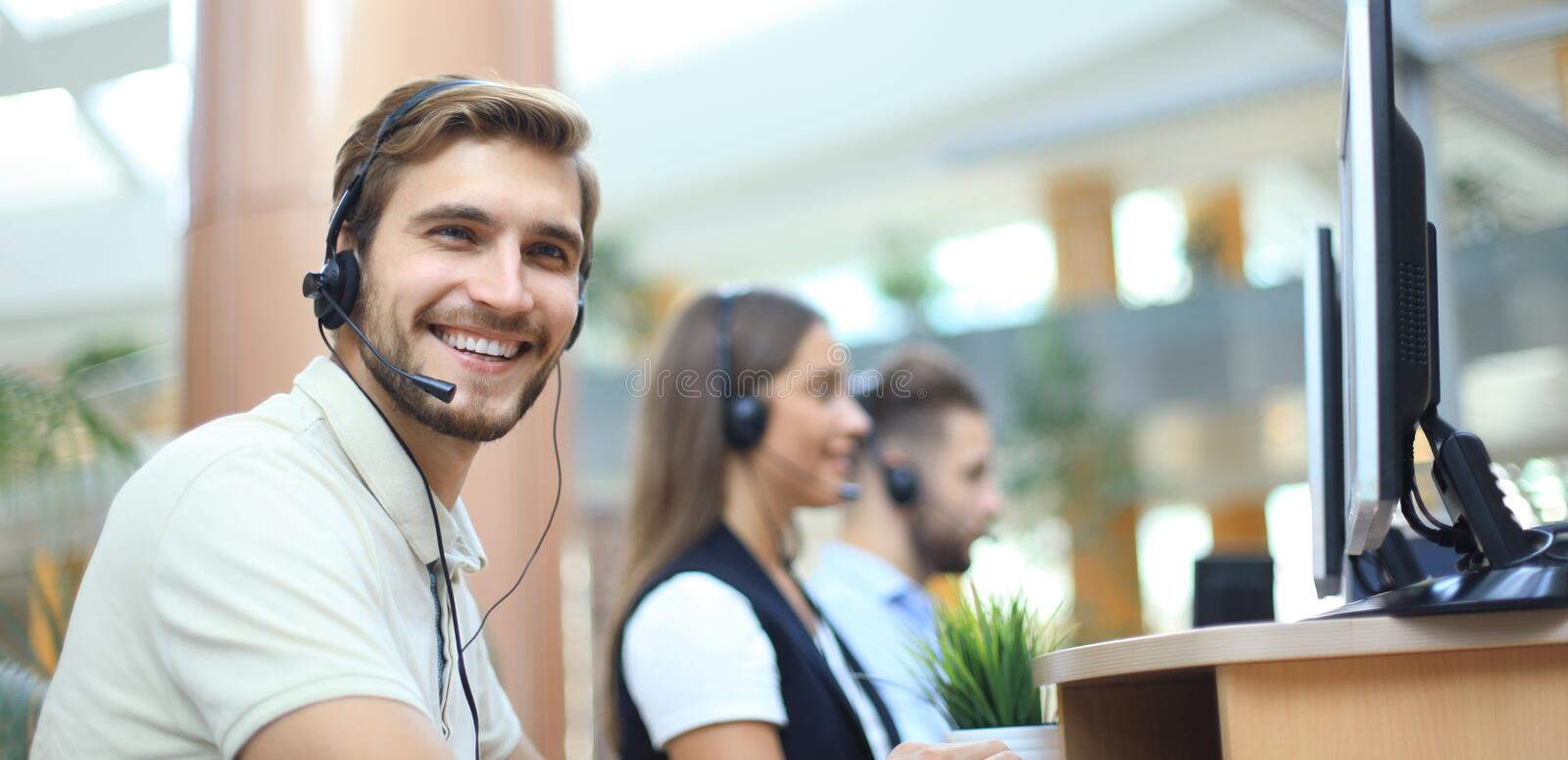 Attractive positive young businesspeople and colleagues in a call center office. royalty free stock photo