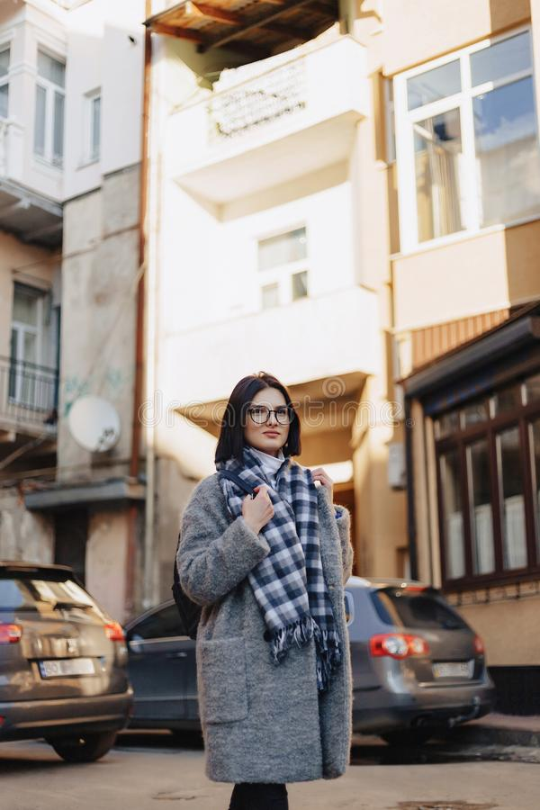 Attractive positive young girl wearing glasses in a coat on the background of buildings on cars stock image