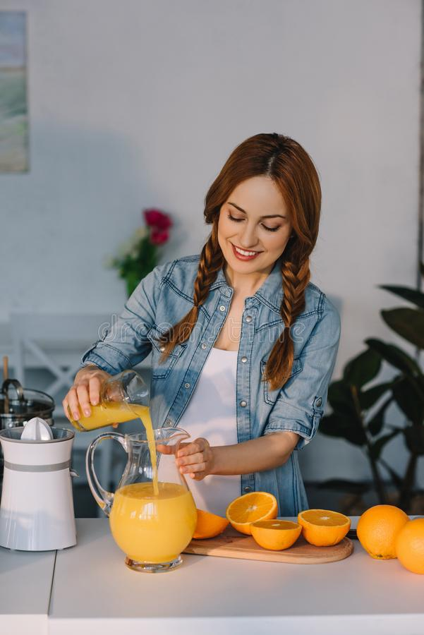attractive pregnant woman pouring orange juice into jug stock images