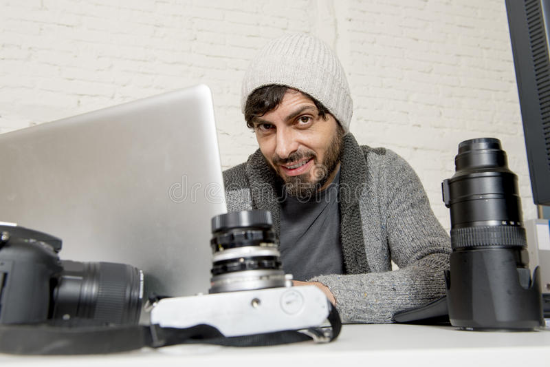 Attractive press photographer man working with laptop computer and desk full of photographic gear. Young attractive press photographer man working with laptop royalty free stock photos