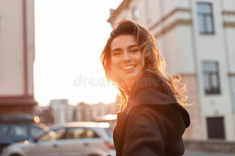 Attractive pretty cheerful young woman in fashionable clothes walks around the city in bright sunny day. European girl smiles. And enjoys the warm spring orange royalty free stock photography