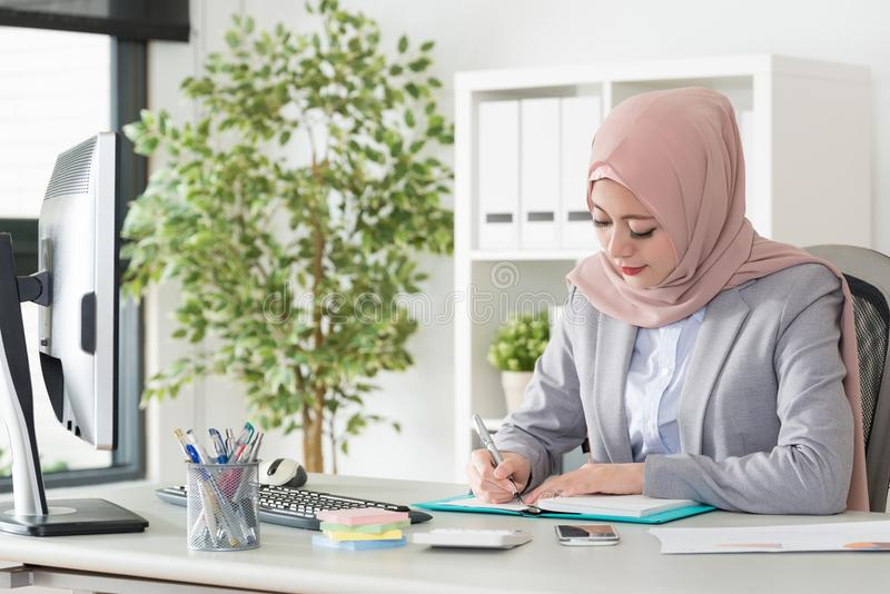 Attractive pretty muslim woman manager using pen royalty free stock image