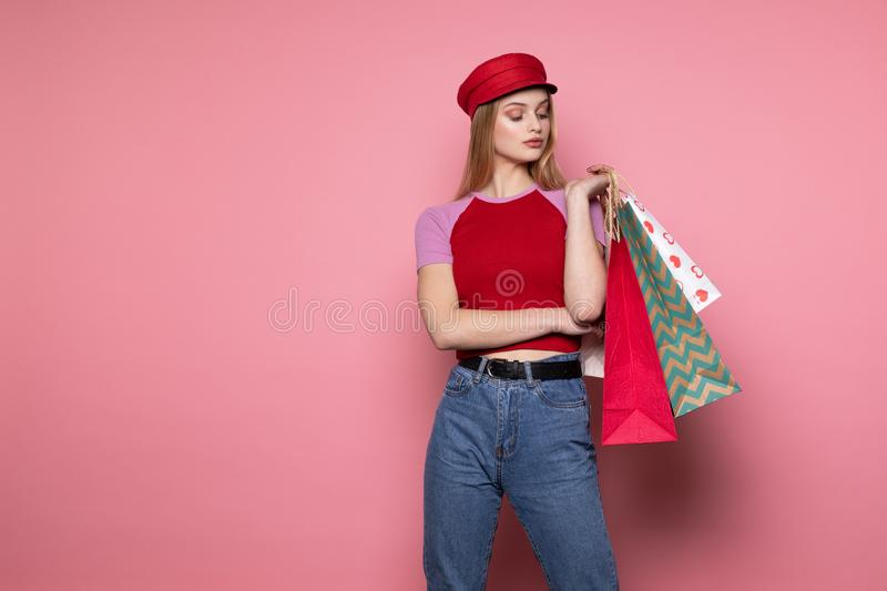 Attractive pretty seriously young female model in stylish red hat standing against pink wall royalty free stock images