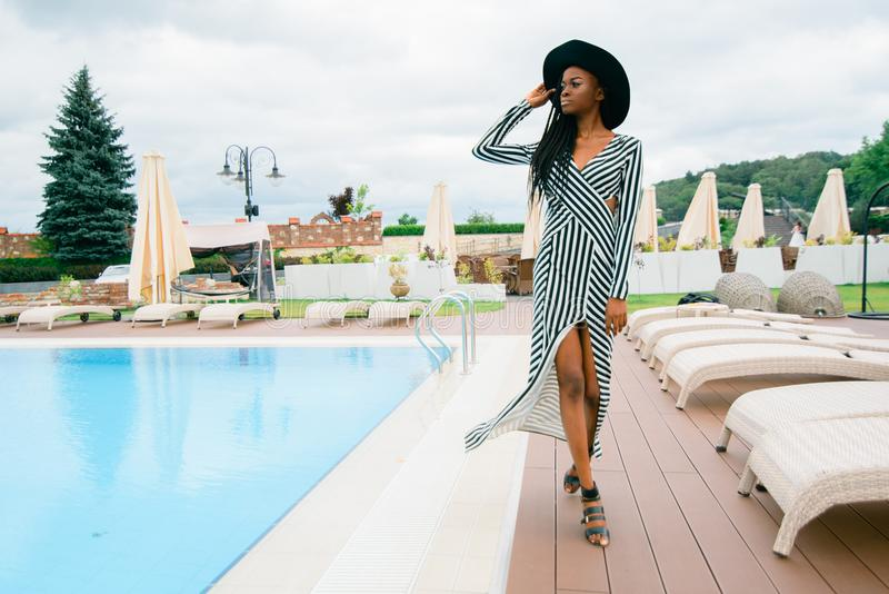 Attractive, pretty, tender, beautiful american woman in long dress in stripes and black hat. Model walking near pool of royalty free stock photos